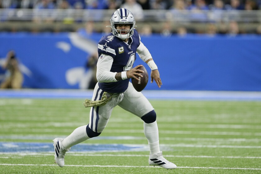Cowboys quarterback Dak Prescott rolls out while looking for a receiver during a game against the Lions.