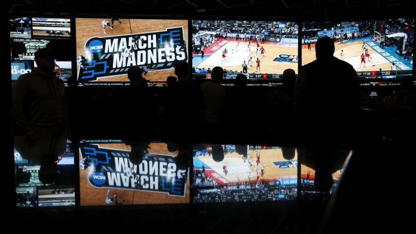 People watch coverage of the NCAA college basketball tournament last March at the Westgate Superbook sports book in Las Vegas.