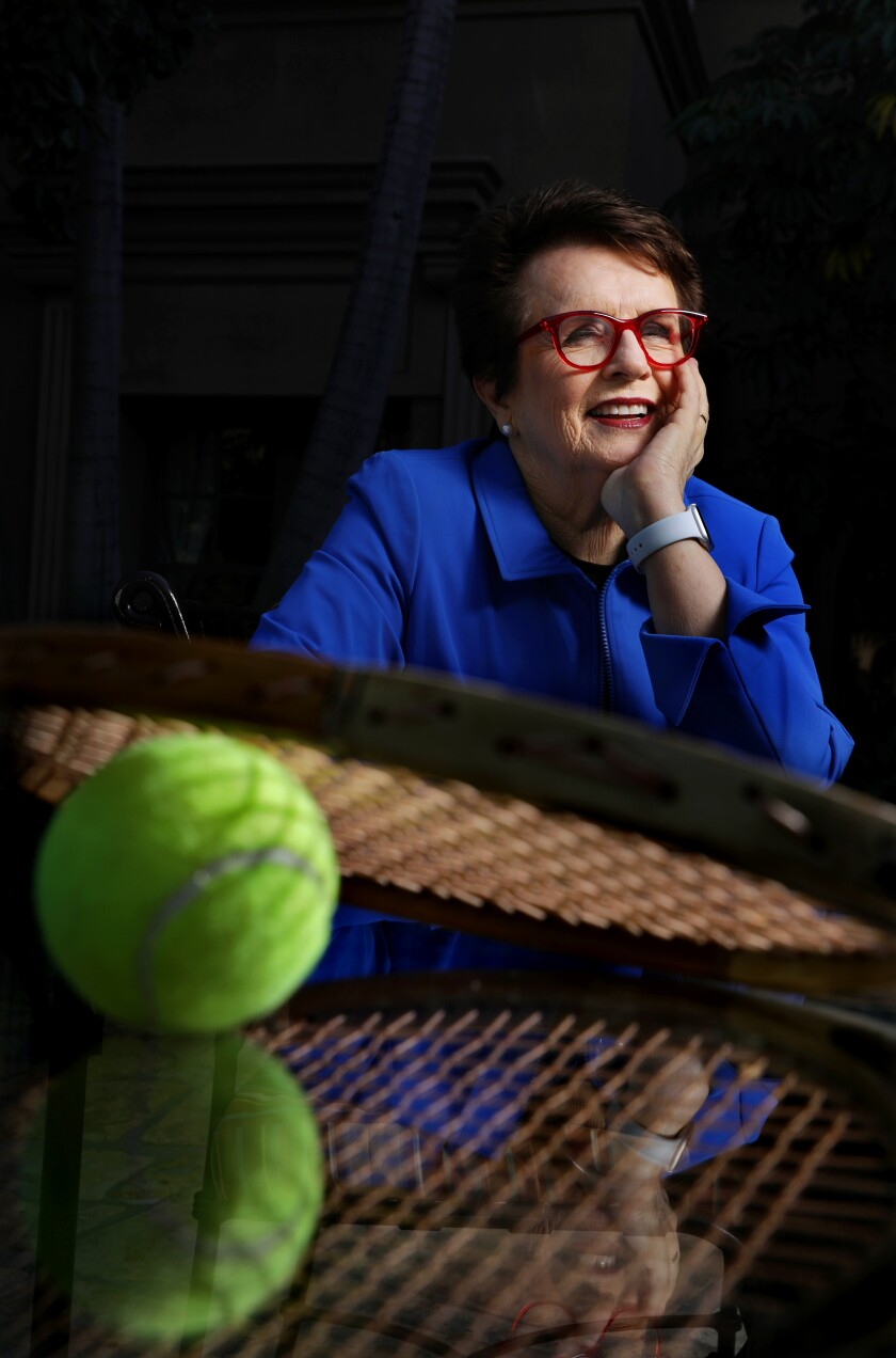 Billie Jean King in a blue jacket, seated, with a tennis ball and racket in the foreground.