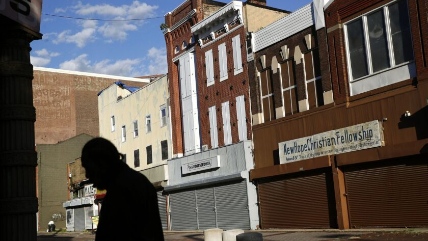 A man walks past vacant storefronts at the Old Town Mall in Baltimore. More than half the neighborhood's residents live in poverty.