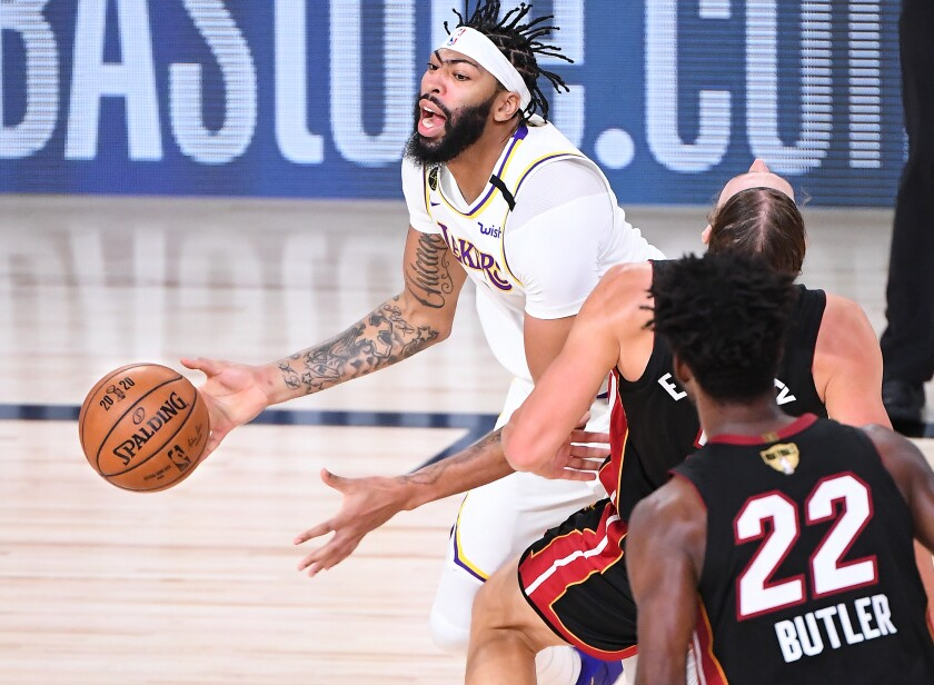 Lakers forward Anthony Davis charges into Heat center Kelly Olynyk for a foul during Game 3 on Sunday night.
