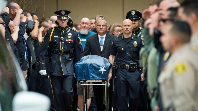 El capitán de la policía de Whittier, Jeff Piper, camina a la derecha junto al cuerpo de su gran amigo y compañero de trabajo, Keith Boyer, quien perdiera la vida en cumpliento de su deber. Michael Owen Baker / For The Times