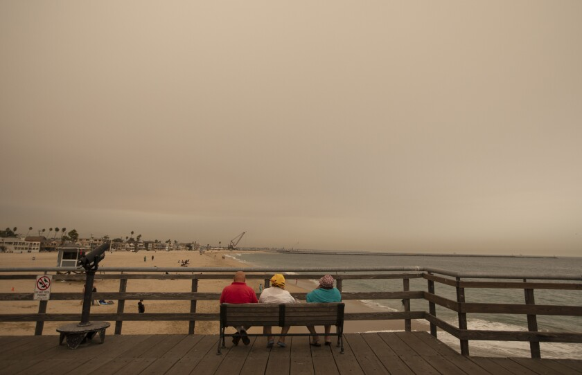 Ash and smoke were in the air over Seal Beach, Calif., on Thursday.