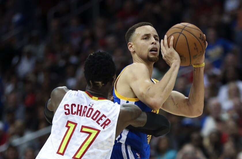 Golden State Warriors guard Stephen Curry (30) shoots as Atlanta Hawks guard Dennis Schroder (17) defends in the second half of an NBA basketball game Monday, Feb. 22, 2016, in Atlanta. Golden State won 102-92. (AP Photo/John Bazemore)