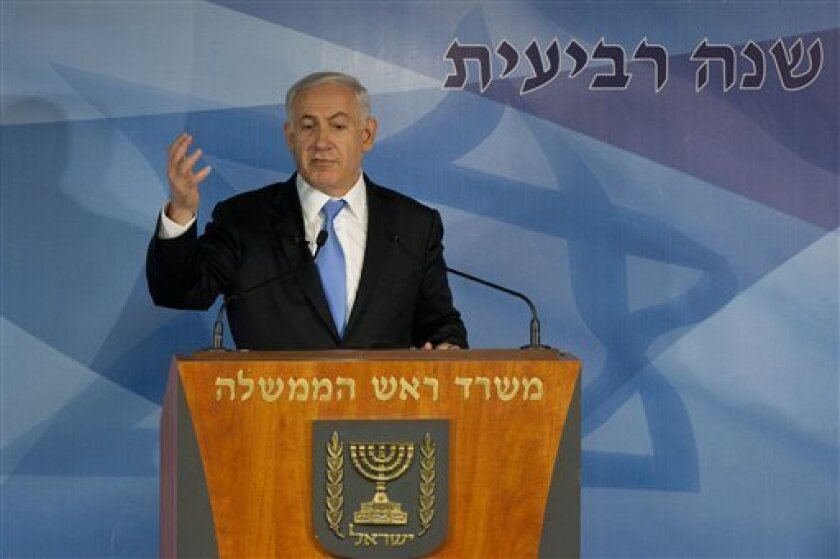 """Israeli Prime Minister Benjamin Netanyahu gives a press conference in Jerusalem, Tuesday, April 3, 2012. Netanyahu said that the planned evacuation of a group of Jewish settlers who illegally occupied a West Bank house has been put on hold. From left to right the Hebrew text reads: """"Prime Minister Office"""", """"4th year"""". (AP Photo/Bernat Armangue)"""