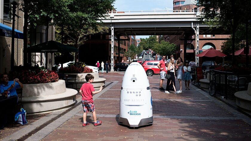 A security robot patrols the pedestrian breezeway of Washington Harbour in Washington, D.C., in September. A model in the San Francisco Bay Area's pilot program has been taken off its beat after some incidents.