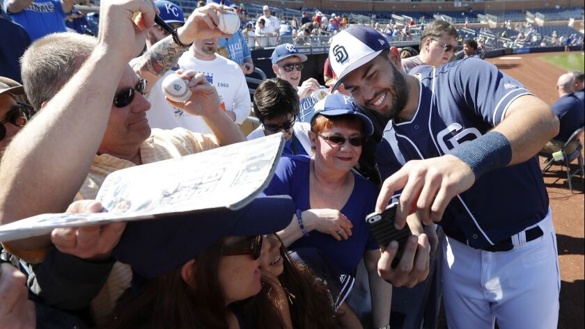 Eric Hosmer poses for a photo with fans before a spring training game.