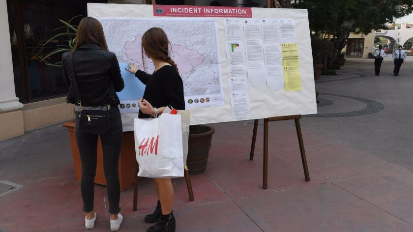 Shoppers on Santa Barbara's main drag, State Street, check a fire incident map Tuesday.