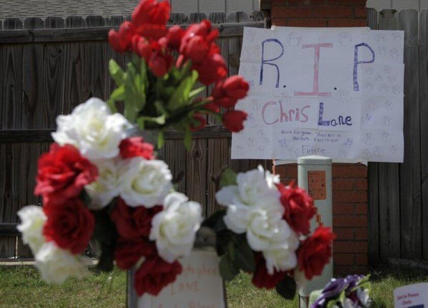A sign hangs on a makeshift memorial for slain Australian college student Christopher Lane, 22, outside the neighborhood where he was killed in Duncan, Okla.