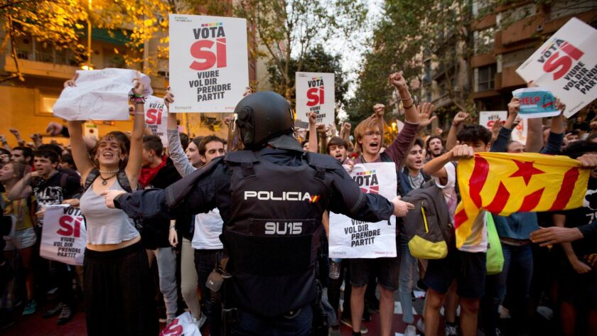 A Spanish national police officer tries to stop demonstrators protesting outside the main offices of