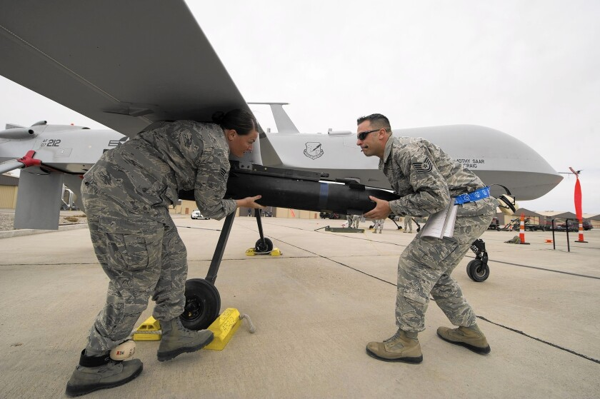 An Air Force crew loads a missile on a Predator drone.