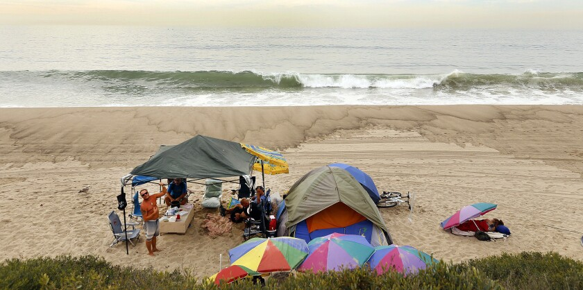 People gather at a collection of tents along Will Rogers State Beach in 2015