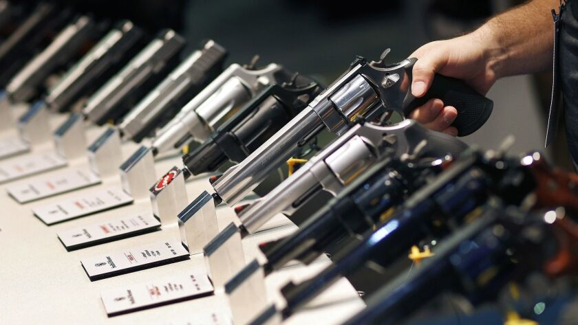 FILE - In this Jan. 19, 2016 file photo, handguns are displayed at a trade show in Las Vegas. With p