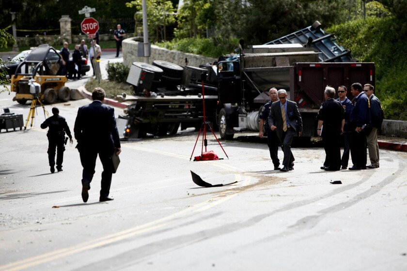 Investigators survey the aftermath of a crash that killed an LAPD officer in Beverly Hills on March 7.