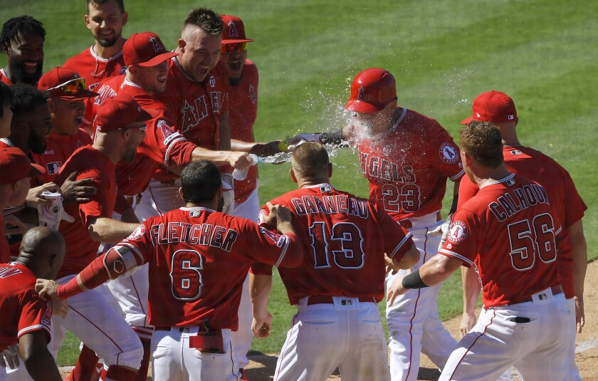 Angels rookie Matt Thaiss is splashed by his teammates while crossing home plate.
