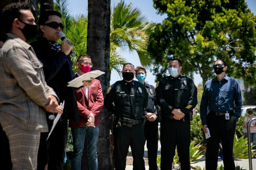 Fernando Z. López, the Executive Director for San Diego Pride, stands alongside La Mesa Police Department officials.