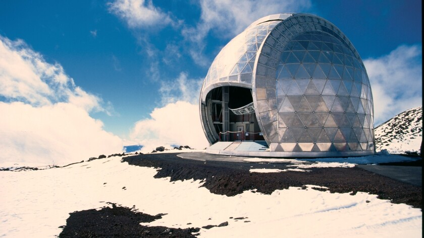 An observatory is perched on snow-covered ground atop Mauna Kea on Hawaii Island.