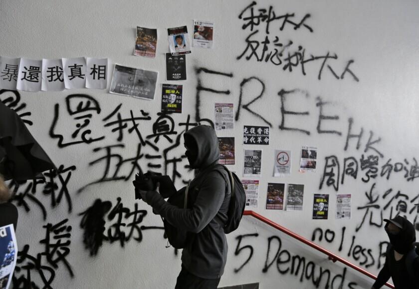 A protester walks past a vandalized wall during an anti-government rally at Hong Kong University of Science and Technology in Hong Kong, Thursday, Nov. 7, 2019. (AP Photo/Dita Alangkara)