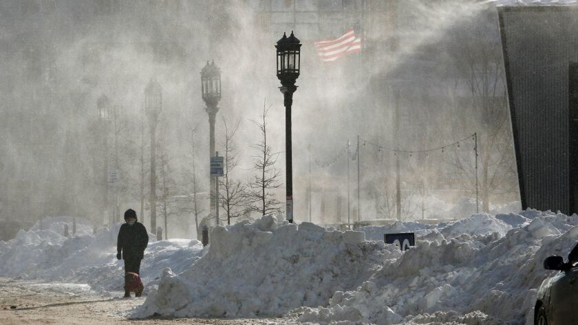 Wind-whipped snow swirls in Boston's Seaport district on Friday.