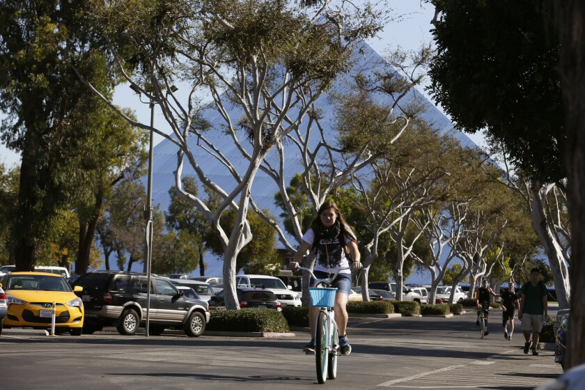 OCTOBER 29, 2015. LONG BEACH, CA. Students ride through a parking lot at Cal State Long Beach. T