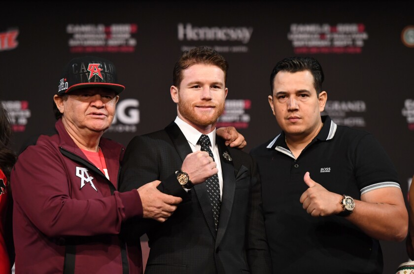"Boxer Canelo Alvarez (C), his manager/trainer Jose ""Chepo"" Reynoso (L) and trainer Eddy Reynoso (R) pose after a news conference at MGM Grand Hotel & Casino on September 12, 2018 in Las Vegas, Nevada. Alvarez will challenge WBC/WBA middleweight champion Gennady Golovkin for his titles in a rematch on September 15 at T-Mobile Arena in Las Vegas."