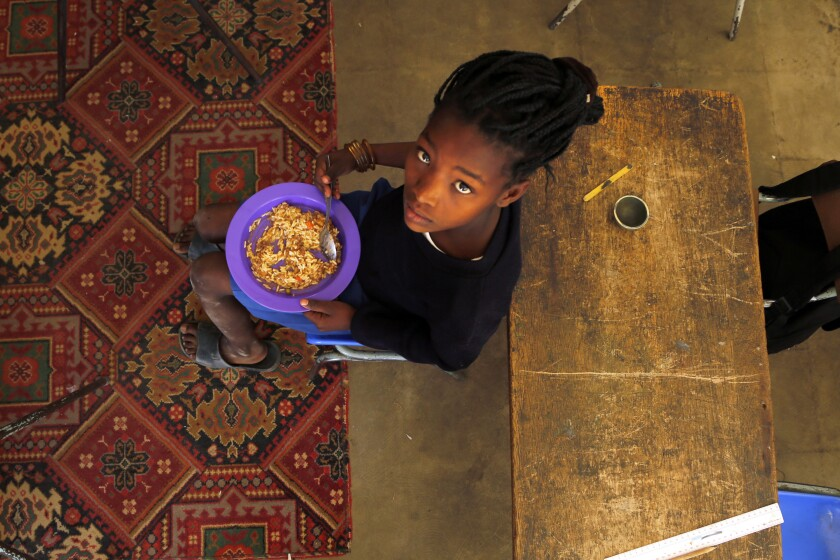 Children share a meal they received from a government-sponsored feeding program in South Africa.