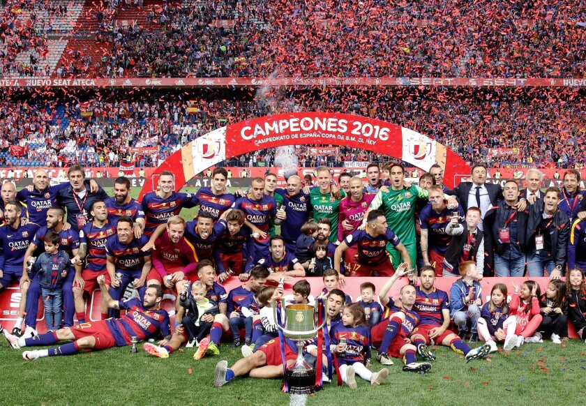 Barcelona's pose with the trophy after they won the final of the Copa del Rey soccer match between FC Barcelona and Sevilla FC at the Vicente Calderon stadium in Madrid, Sunday, May 22, 2016. Barcelona won 2-0. (AP Photo/Daniel Ochoa de Olza)