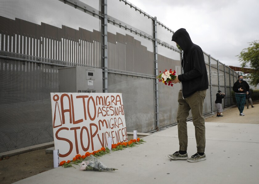 A man puts flowers down during a vigil calling for an independent investigation into a fatal shooting by the Border Patrol.