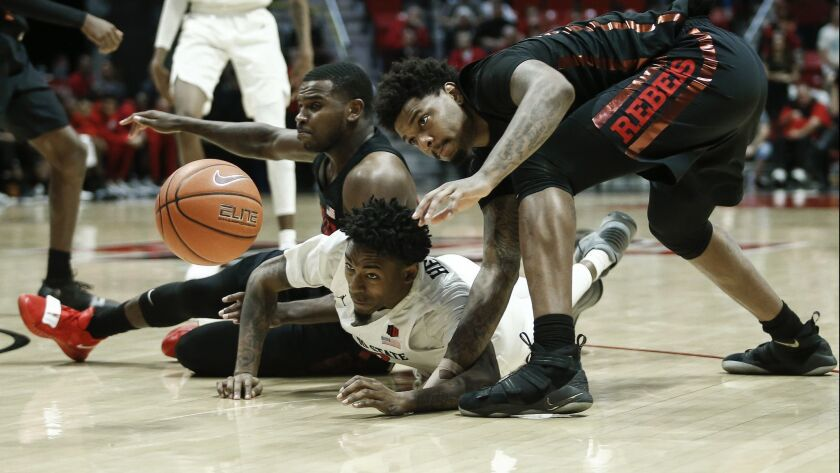 SDSU's Jeremy Hemsley (center) dives for a loose ball with UNLV's Amauri Hardy (left) and Tervell Beck (right) during the Aztecs' 94-77 win at Viejas Arena on Saturday.