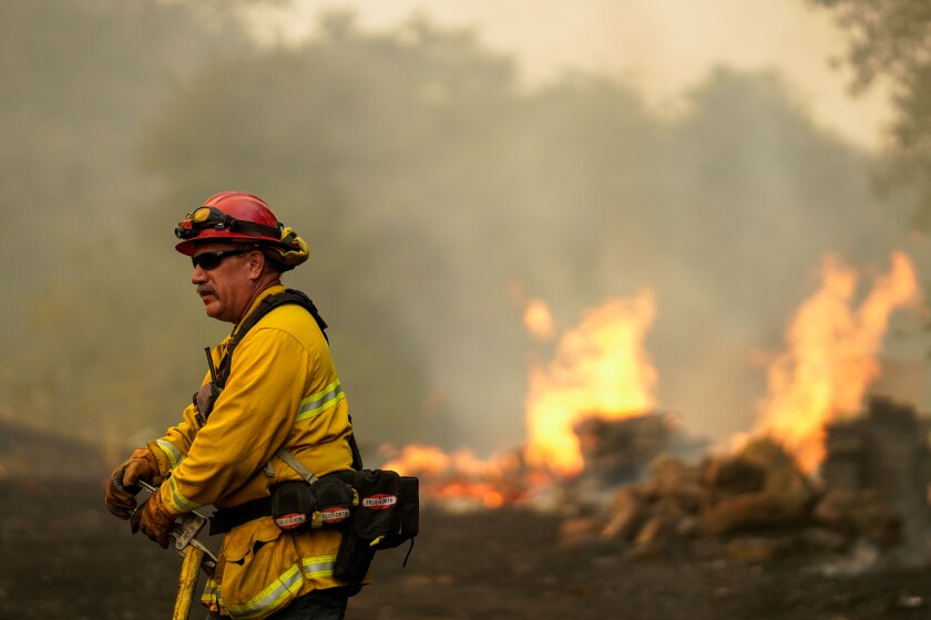 Flames leap in the background as a firefighter battles the Hennessy fire in Vacaville, Calif.