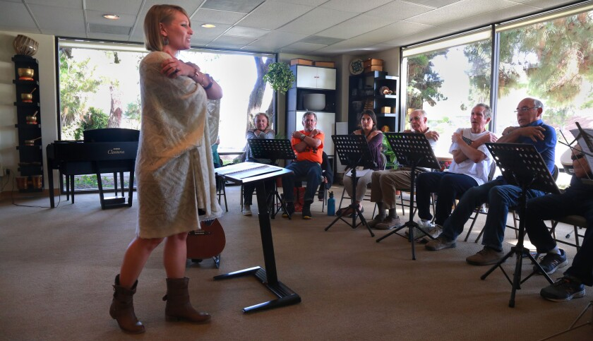 Music therapy instructor Lindsay Zehren leads the class in breathing exercises at the conclusion of a harmonica class for people suffering symptoms from Parkinson's Disease.
