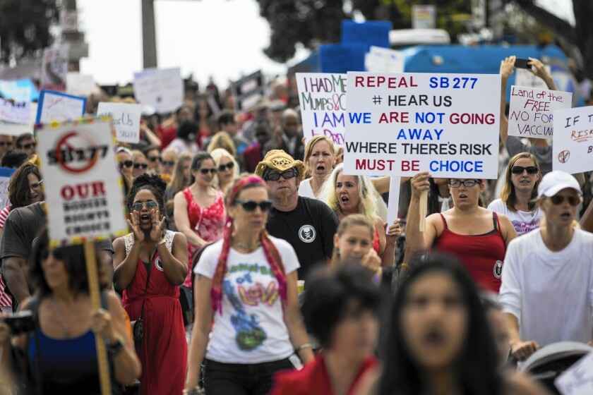 Several hundred opponents of California's new vaccination law march from the Santa Monica Pier to City Hall on Friday.