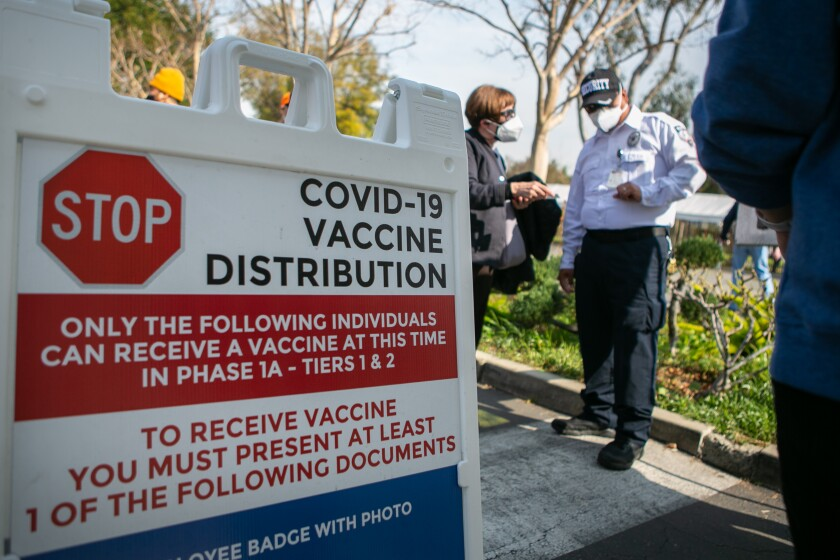 A woman stands next to a security officer near a sign with information about COVID-19 vaccine distribution.