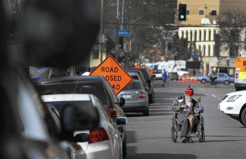 A Navy veteran pushes his wheelchair backward in skid row.