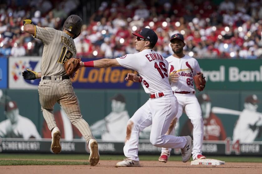 Tommy Edman, el segunda base de los Cardenales de San Luis, toca a Adam Frazier, izquierda, de los Padres de San Diego