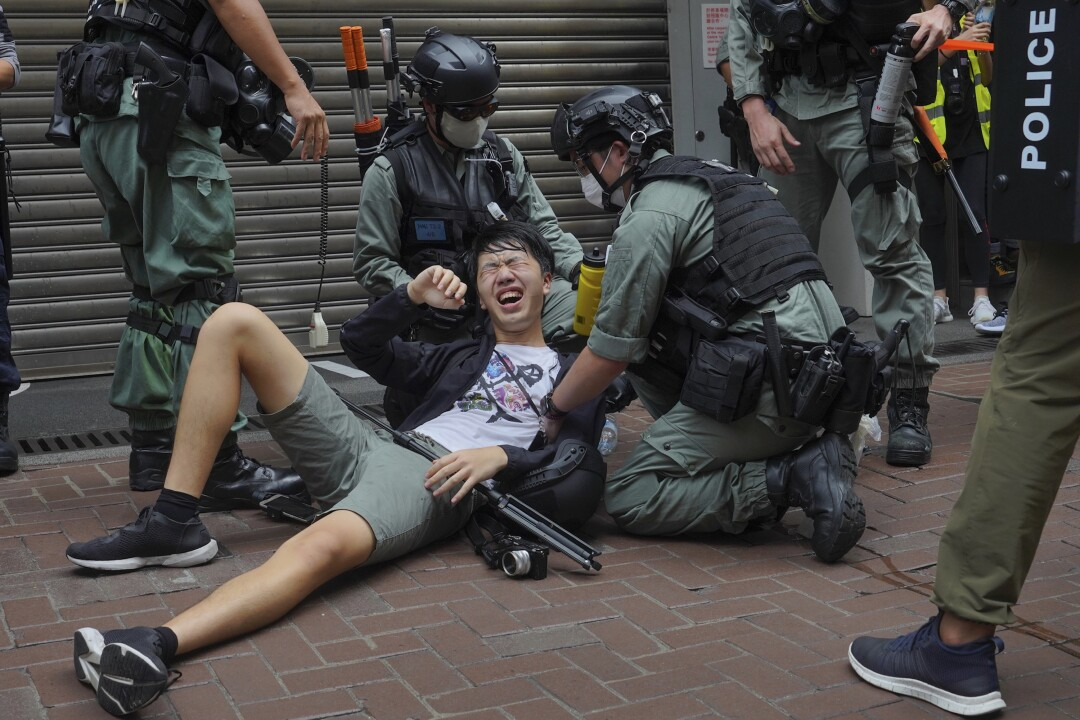 A reporter falls to the ground after being pepper sprayed by Hong Kong police during a protest in Causeway Bay on Wednesday.