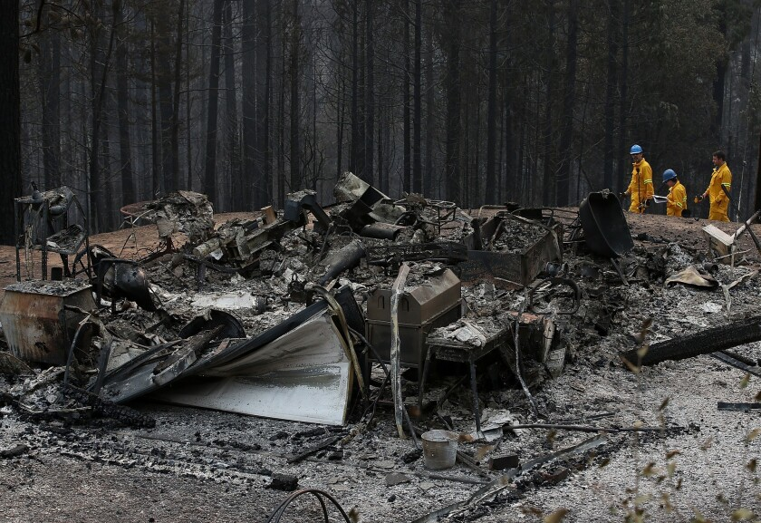 Officials inspect a structure that was destroyed by the King fire on Friday, Sept. 19, near Pollock Pines in northern California.
