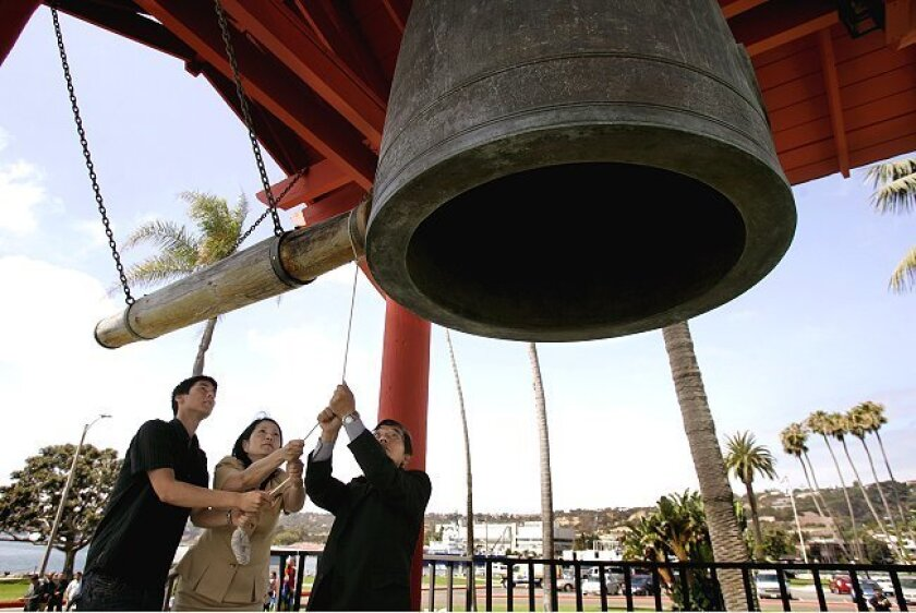 Ringing the Yokohama Friendship Bell at a ceremony on Shelter Island marking the anniversary of the atomic bombing of Nagasaki are Hiroshima survivor Mike Kawamura (right), Akiko Mikamo and her son Andrew Flores, 20. Mikamo's father was badly burned in the Hiroshima bombing.