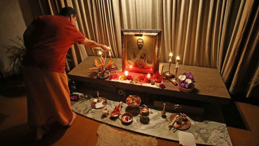 Swami Dhyanayogananda lights candles to the Sri Ramakrishna shrine at the Ramakrishna Monastery in T