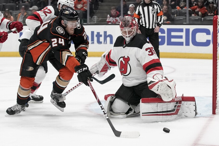 New Jersey Devils goaltender Cory Schneider, right, blocks a shot by Anaheim Ducks center Carter Rowney during the second period of an NHL hockey game in Anaheim, Calif., Sunday, March 1, 2020. (AP Photo/Chris Carlson)
