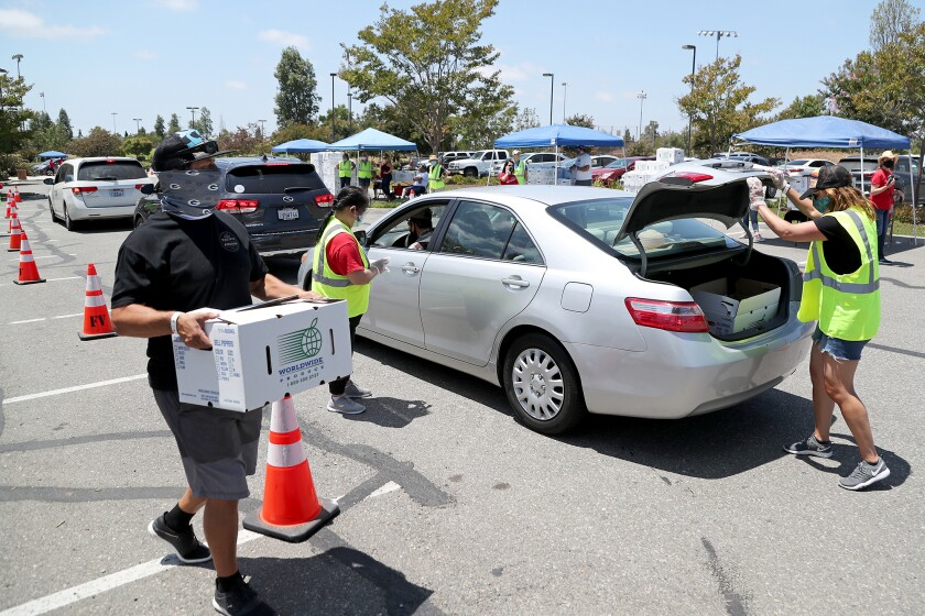 Volunteers help load Worldwide Produce pre-boxed groceries  during a drive-through food giveaway.