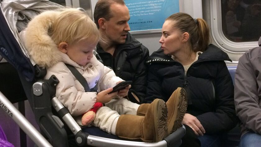 A child plays with a smartphone while riding the subway in New York.