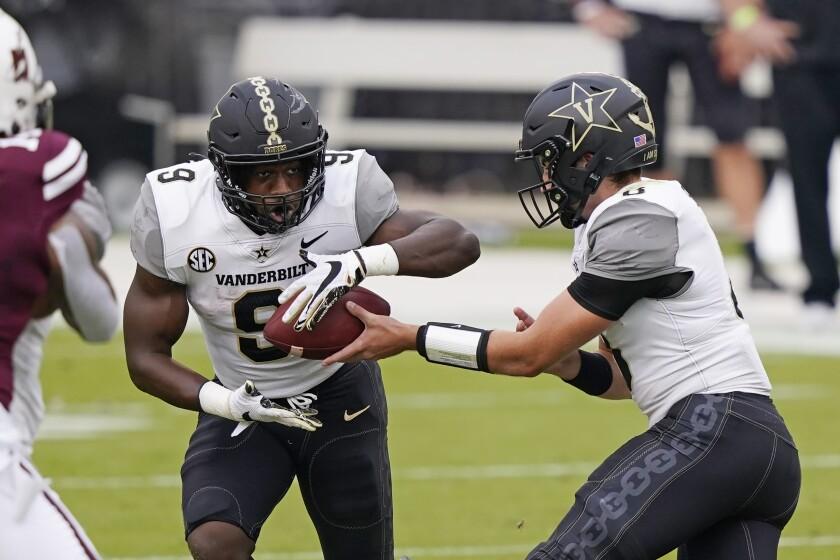 Vanderbilt running back Rocko Griffin (9) takes a handoff from Vanderbilt quarterback Ken Seals (8) during the first half of an NCAA college football game against Mississippi State in Starkville, Miss., Saturday, Nov. 7, 2020. (AP Photo/Rogelio V. Solis)