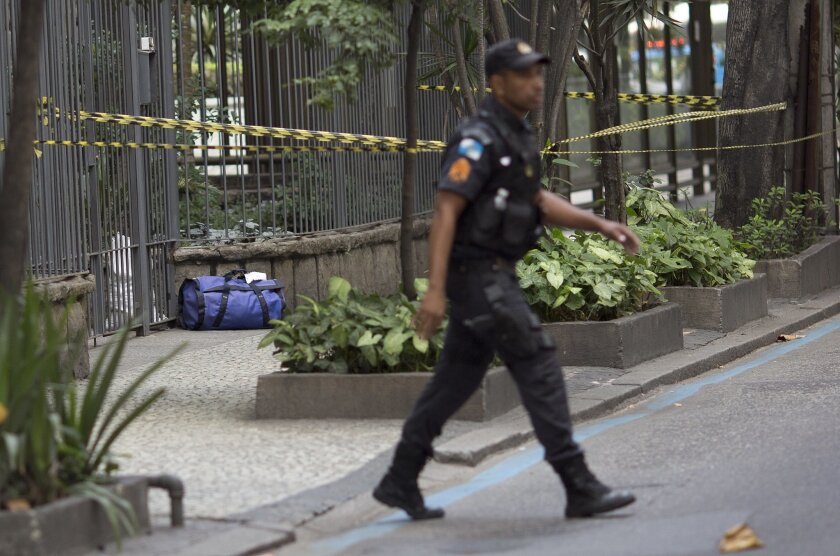 A police officer walks near a backpack deemed suspicious that was left at the door of an apartment building, in the Leblon neighborhood of Rio de Janeiro, Brazil, Monday, July 18, 2016. With the Olympics set to start on Aug. 5, the games and the city have been overshadowed by security threats, viol