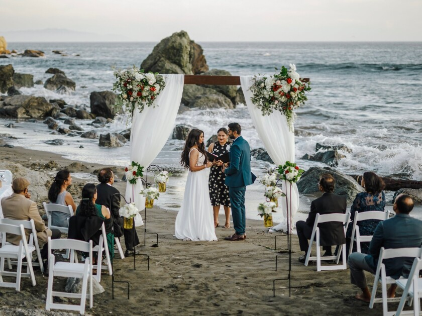 This photo shows bride Namisha Balagopal and groom Suhaas Prasad getting married in a small legal ceremony Aug. 15, 2020, on Muir Beach near San Francisco. The couple plans a larger traditional South Asian Indian wedding this August in Utah amid a boom in post-vaccination nuptials around the world. (Vellora Productions via AP)