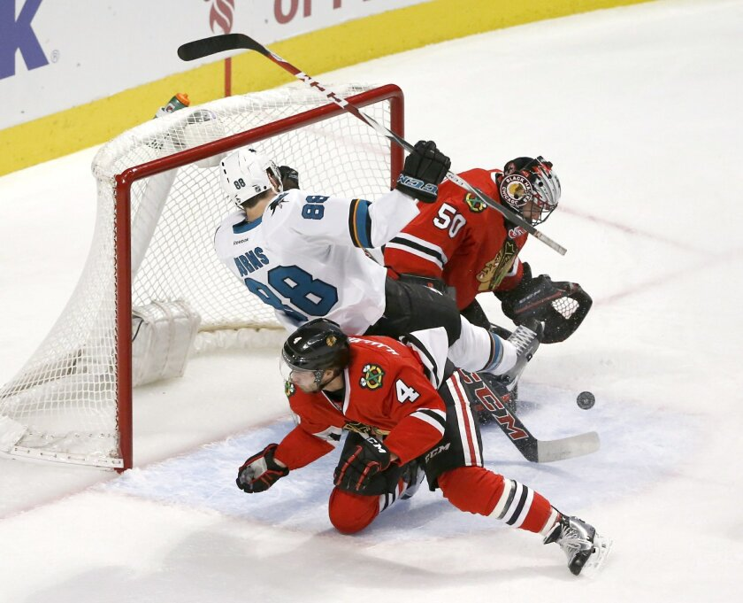 San Jose Sharks defenseman Brent Burns (88) falls over Chicago Blackhawks defenseman Niklas Hjalmarsson (4) as goalie Corey Crawford (50) makes a save on Burns' shot during the second period of an NHL hockey game Tuesday, Feb. 9, 2016, in Chicago. (AP Photo/Charles Rex Arbogast)