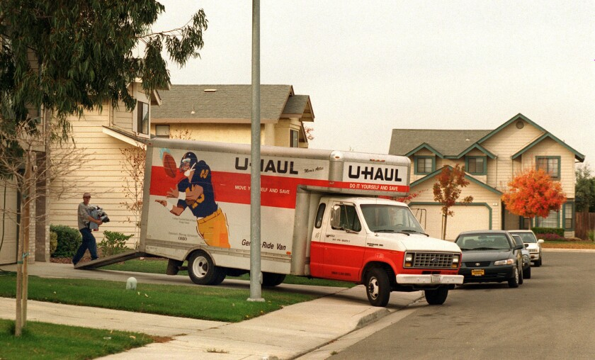 A man carries items up a ramp into a U-Haul truck parked in a driveway.