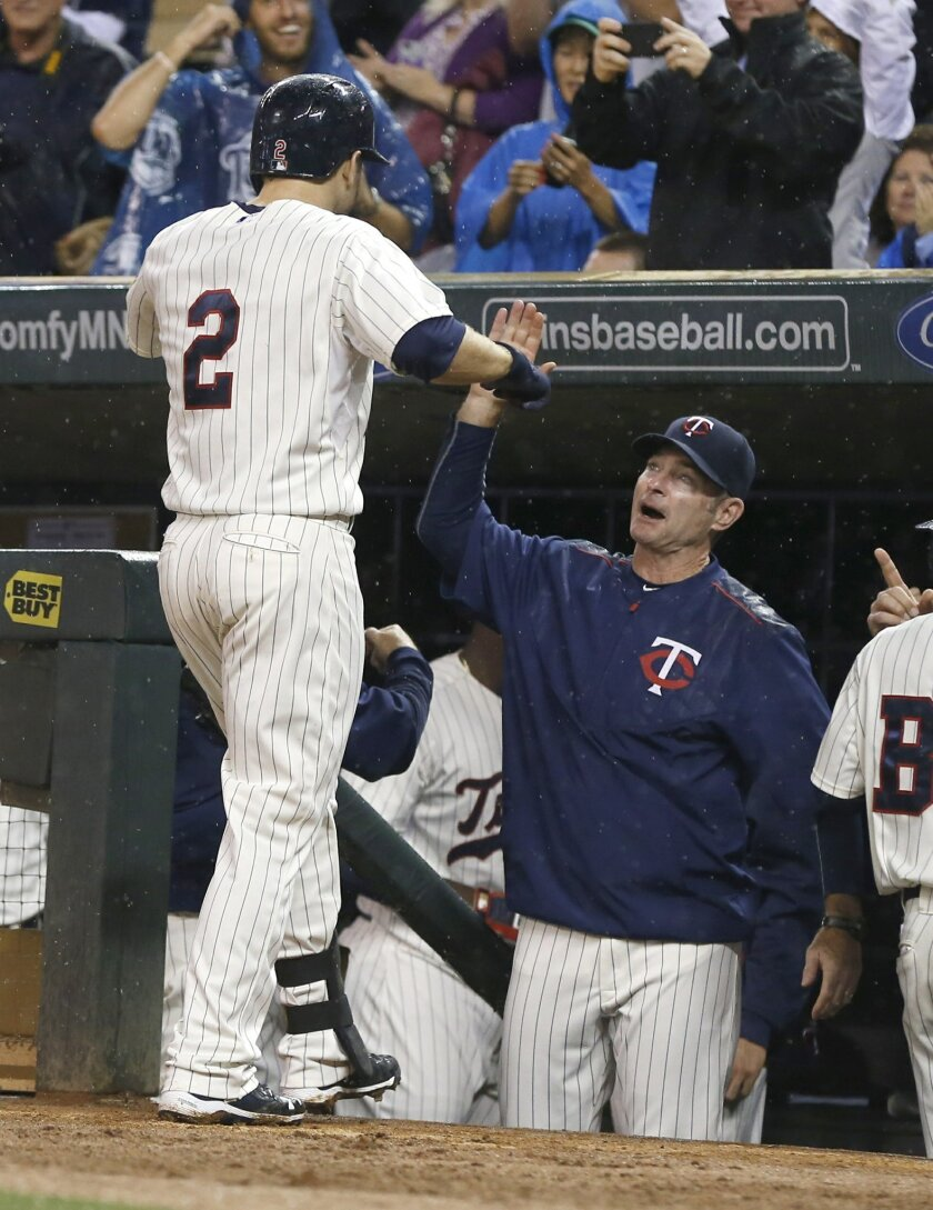 Minnesota Twins' Brian Dozier is greeted by manager Paul Molitor after his solo home run off Cleveland Indians pitcher Corey Kluber in the fourth inning of a baseball game, Wednesday, Sept. 23, 2015, in Minneapolis. (AP Photo/Jim Mone)