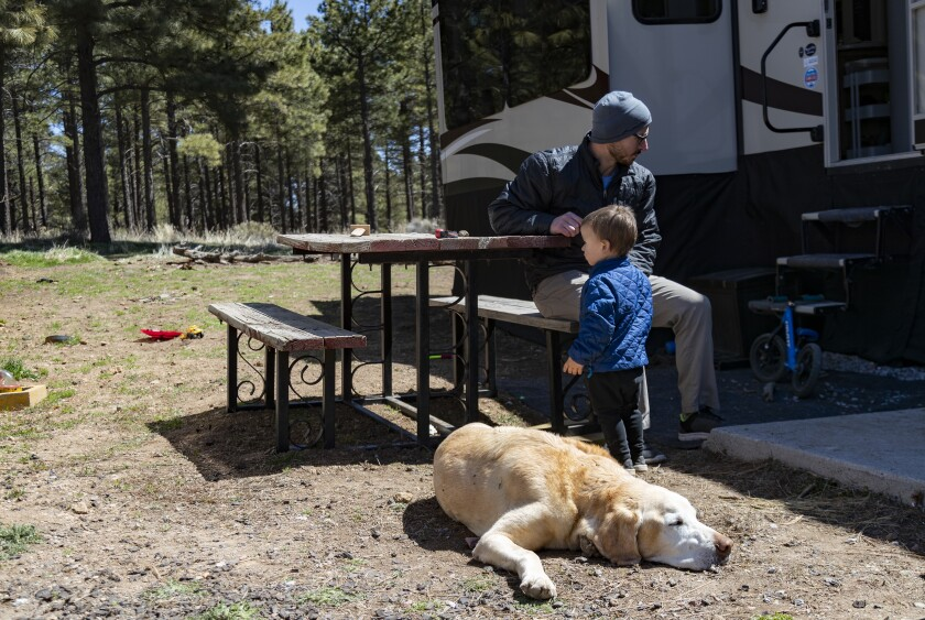 Cody Taylor spends time with his son and dog at Black Bart's RV Park in Flagstaff.