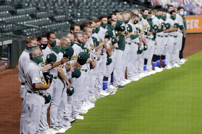The Oakland Athletics stand during the national anthem before playing the Houston Astros.